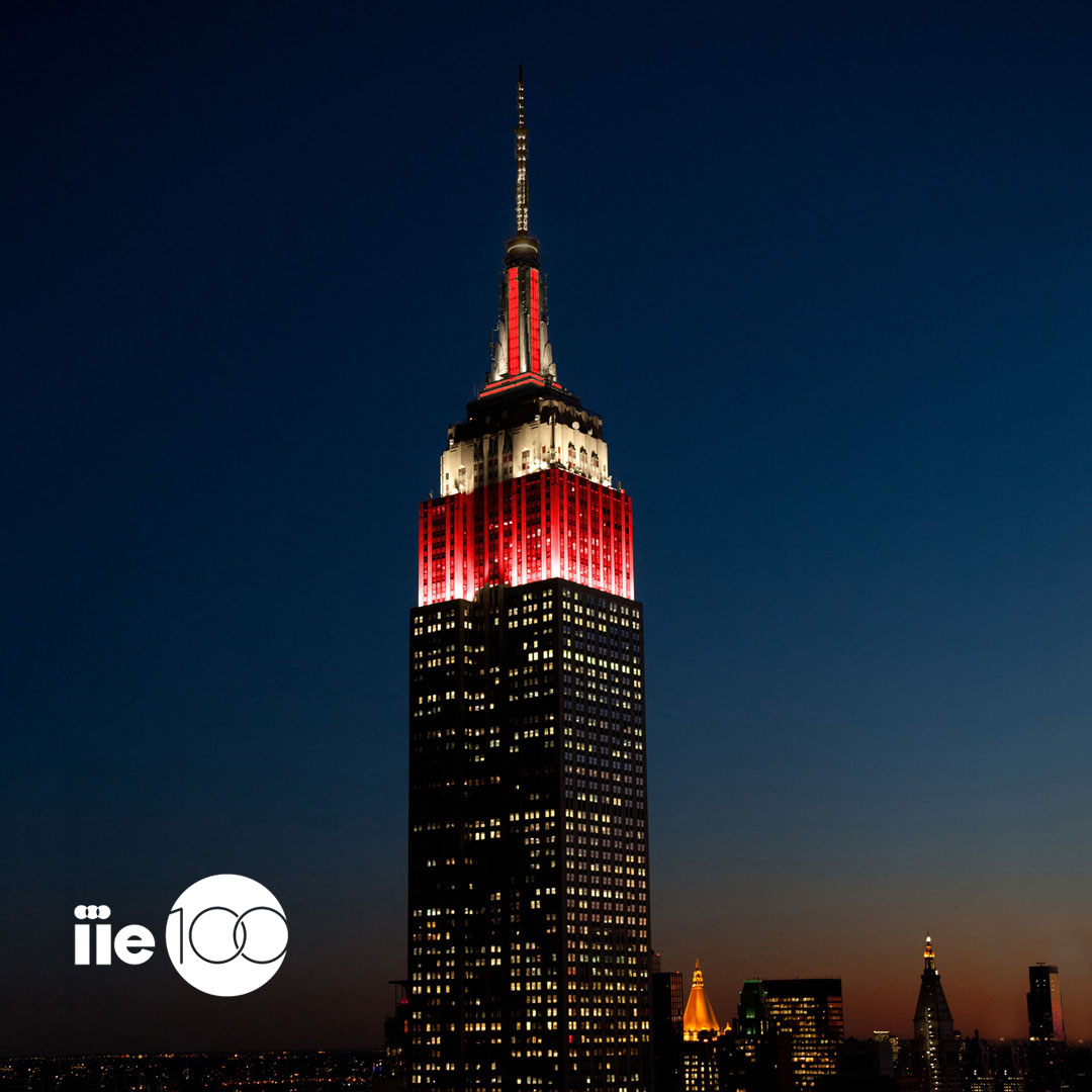 Empire State Building in White and Red with IIE 100 Logo