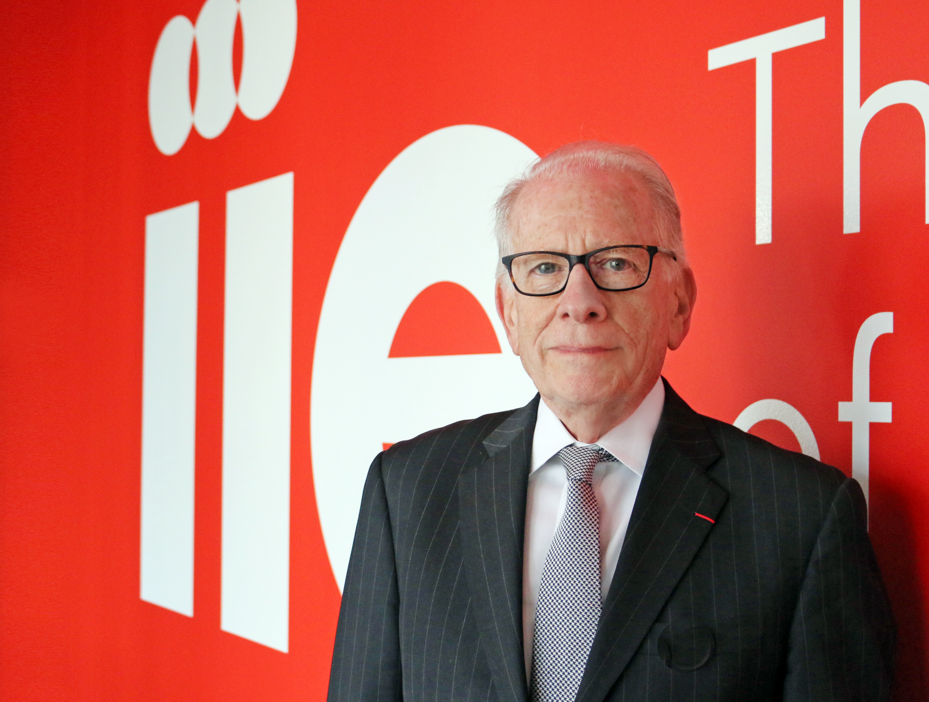Dr. Allan Goodman, President and CEO, standing in front of an IIE logo wall.