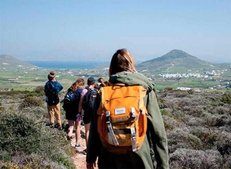 Students wearing backpacks hike along a path with a mountain in the background.